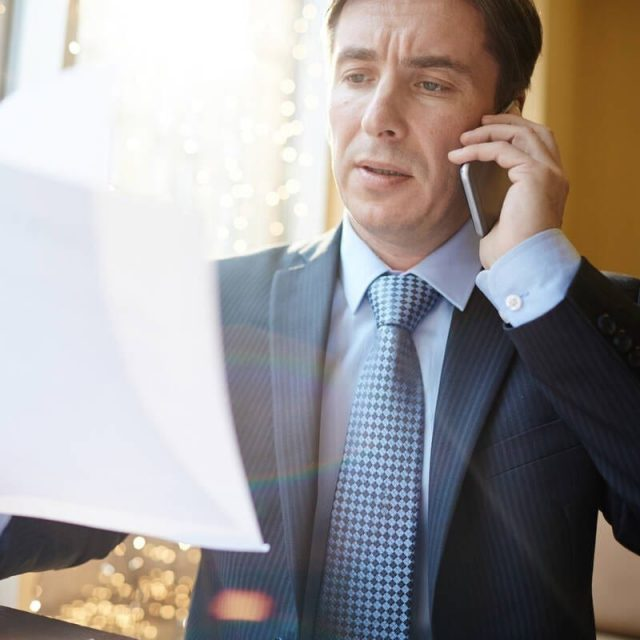 Employer with resume talking to candidates on the phone