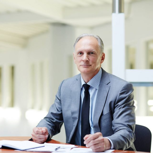 Mature boss in formalwear sitting by his workplace in office and planning work