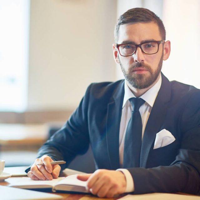 Confident trader in elegant suit sitting in cafe