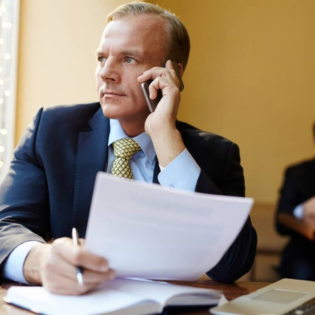 Business leader with document consulting client by cellphone